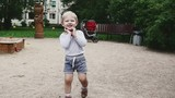 Little boy in shorts walks on playground in summer day. Smile. Childhood. Happy. Slow motion