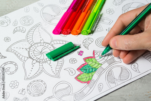 Woman coloring the coloring book for adults with abstract patterns, colored pens
