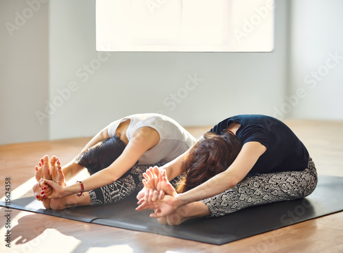 Poster Two young women doing yoga asana seated forward bend