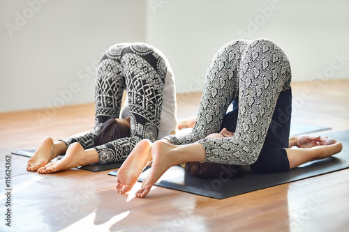 Poster Two young women doing yoga asana easy plow pose