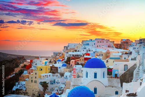 fototapeta na ścianę cityscape of Oia, traditional greek village of Santorini, with blue domes of churches at sunset, Greece, toned