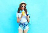Pretty woman drinks fruit juice from cup using smartphone over c