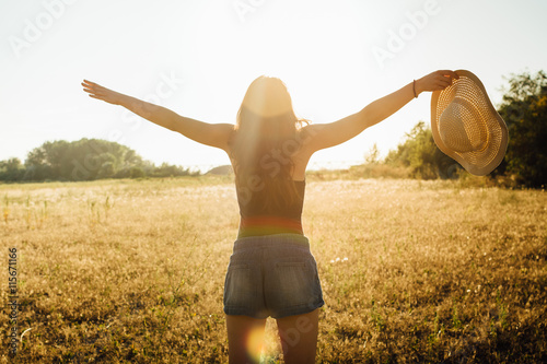 Poster Hippie girl in nature, holding hat looking at Sun