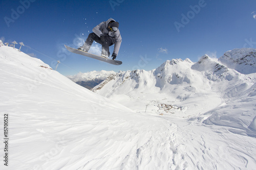 obraz PCV Snowboard rider jumping on mountains. Extreme snowboard freeride sport.