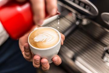 Closeup of barista pouring milk into art cappuccino
