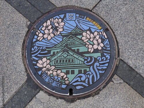 In de dag Tunnel A manhole cover in Osaka, Japan. The Osaka castle and sakura engraved on to a manhole cover as a symbol of an important city's landmark.