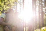 Family in woods embracing with sunlight