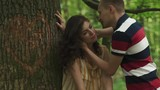 Young beautiful couple lovingly look at each other and kissing on background of heart carved on a tree in green spring forest