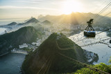 Bright misty view of the city skyline of Rio de Janeiro, Brazil with a Sugarloaf (Pao de Acucar) Mountain cable car passing in the foreground