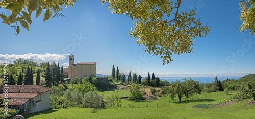 Blick durch Zweige auf die Dorfkirche Sasso, Oberitalien
