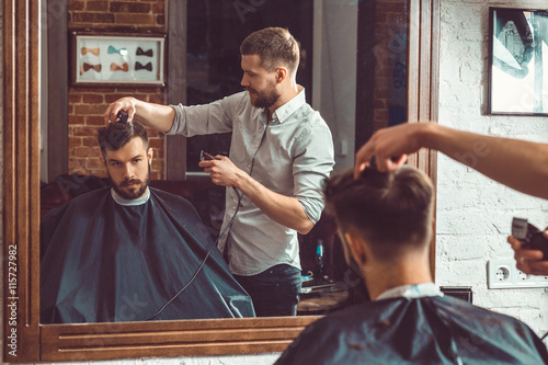 obraz lub plakat Young handsome barber making haircut of attractive man in barbershop
