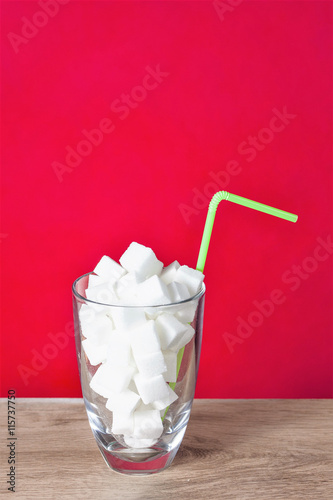Poster Glass with straw full of sugar and sugar cubes on red background