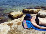 abbronzatura al sole sugli scogli di mare