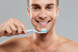 Closeup happy young man holding toothbrush with toothpaste
