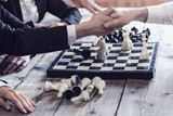Business people playing chess