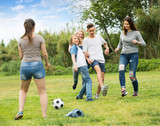 Teenagers playing football in park .