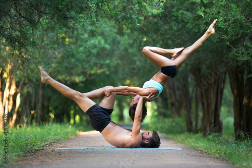 Acro yoga, two sporty people practice yoga in pair, couple doing stretching exer
