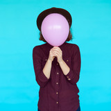 Fototapety Young hipster woman holding balloon over her face