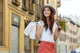 Beautiful summer woman goes shopping in the city