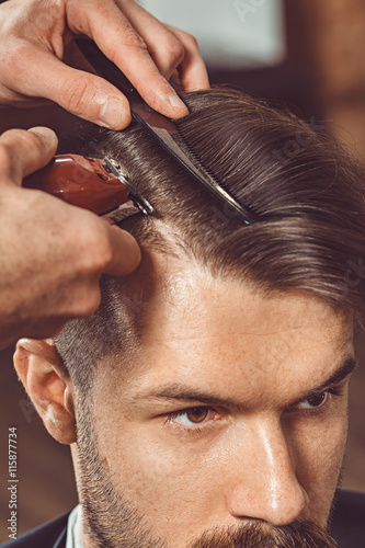 The hands of young barber making haircut to attractive man in barbershop Poster