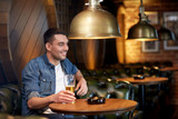 happy man drinking draft beer at bar or pub