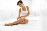 Woman Body Care. Beautiful Girl Touching Long Legs Soft Skin
