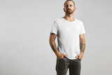 Fototapety Attractive brutal tattooed bearded guy poses in black jeans and blank white t-shirt from premium thin summer cotton, isolated on white mockup