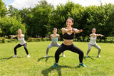 Delighted smiling women doing sport exercises outdoors.