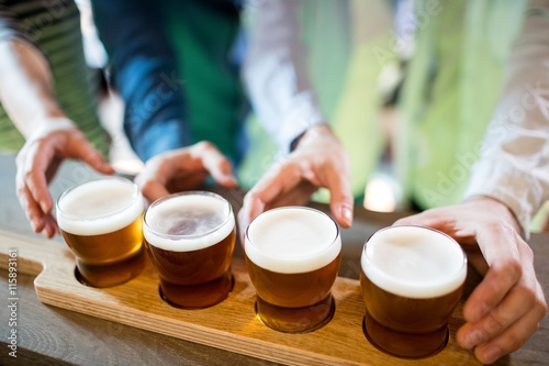 Friends reaching towards beer sampler on counter Poster