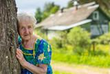 An elderly woman was leaning against a tree near the farmhouse.
