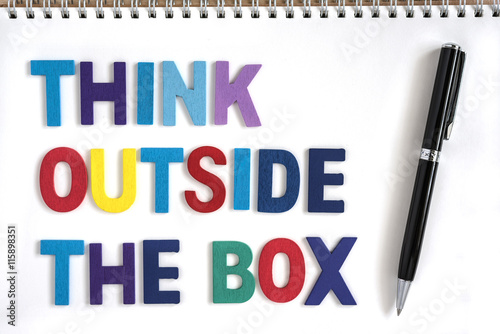 Colorful wood letters word think outside the box in open notebook with a pen Quotes business concept Photo by waewkid