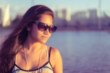 Pretty young woman in thoughtful pose wearing glasses, late evening sunshine over water