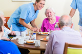 Fototapety Group of seniors having food in nursing home