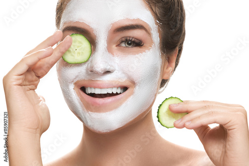 Poster, Tablou Woman with facial mask and cucumber slices in her hands