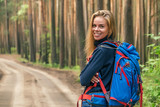 Happy beautiful girl with backpack in forest