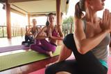 Women doing yoga in twist pose on mat