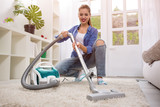 Beautiful young woman cleaning with vacuum cleaner