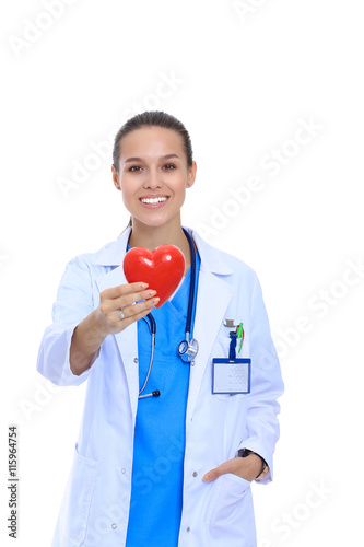 Zdjęcia na płótnie, fototapety, obrazy : Positive female doctor standing with stethoscope and red heart symbol isolated