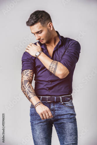 1aaf1b3ef27 Handsome young man in blue shirt and jeans posing on white background in  studio