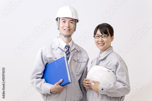 ファイルとヘルメットを持ちカメラ目線の男女作業員