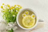 Chamomile tea with lemon slice and flowers