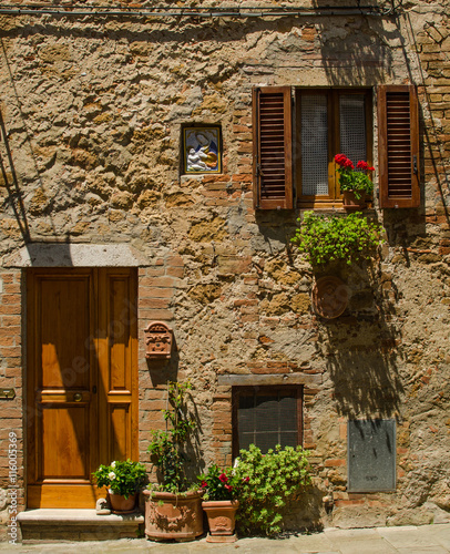 A house with window and door with flowers of Pienza, Italy