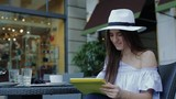 Young Attractive Woman in Hat, Sitting in a Street Cafe and Typing on Tablet.