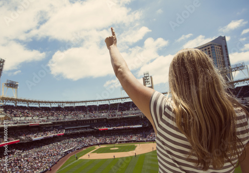 Woman standing and cheering at a baseball game