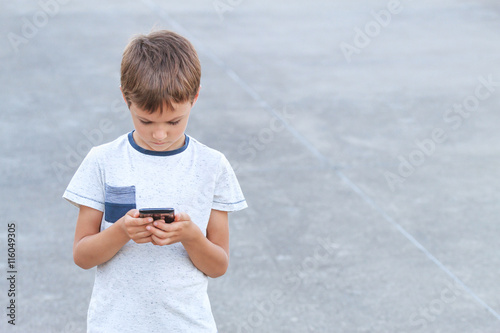 Poster Boy with smartphone texting message, playing game, using apps
