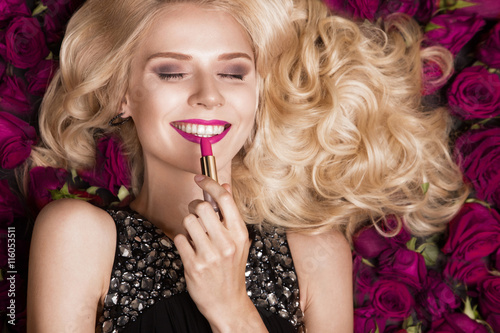 Poster Beautiful blond girl lying on background of roses