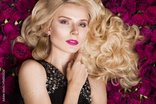 Tela Beautiful blond girl lying on background of roses