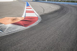Texture of motor race asphalt and red white curb. Close up on Grand Prix street circuit