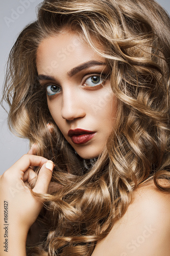 Beautiful girl with long wavy hair . fair-haired model with curl Plakat