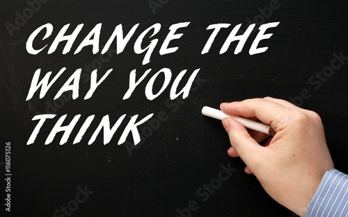 Hand writing the words Change The Way You Think in white chalk text on a blackboard